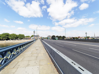 A bright summers day with light traffic crossing Trent Bridge in Nottingham