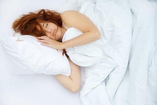 Draufsicht einer attraktiven, jungen, rothaarigen Frau, Ginger,die entspannt im Bett ein weiches weißes Kissen in den Armen, schläft, genießt frische weiches Bett mit freiem Raum für Ihren Text