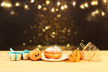 Image of jewish holiday Hanukkah with wooden dreidels (spinning top) and donut on the table.