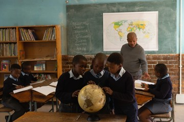 Schoolkids using globe in classroom