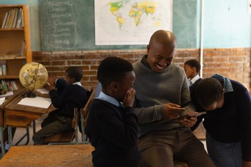 Male teacher using digital tablet with students in classroom