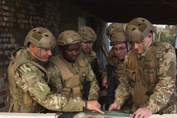 Military men talking over map