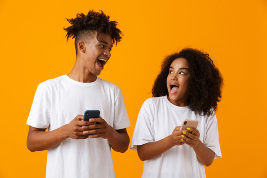 Emotional happy young cute african couple isolated over yellow background using mobile phones.