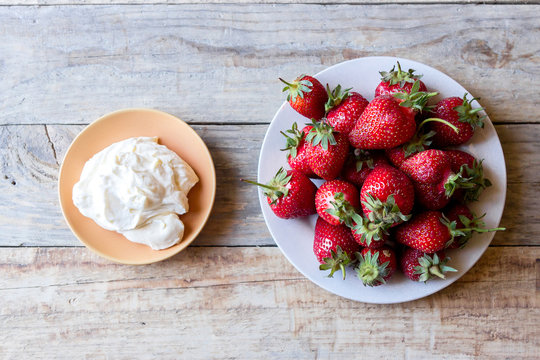 fresh juicy red strawberry with whipped cream on a wooden table