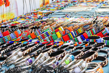 Colorful beads and leather handmade bracelets, bangles and necklaces at local craft market in South Africa. Traditional african souvenirs. Ethnic tribal design and pattern