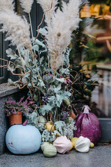 Stylish and elegant fall farmhouse decor ideas. Blue and purple colored pumpkins, dry oak leaves. Minimalism artful concept