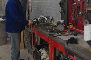 Male mechanic grinding machine in garage