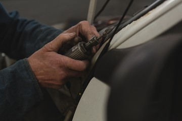 Male mechanic using mini drill machine