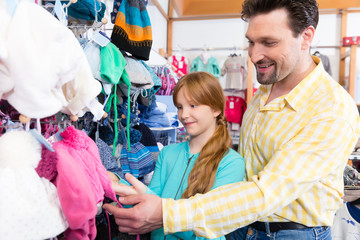 Portrait of smiling father and daughter shopping clothes in retail store