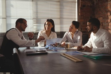Executives discussing over document in conference room