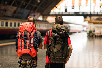 couple  traveler with backpack waiting for train, Asian backpacker with hat standing on railway platform at Bangkok train station. Holiday, journey, trip and summer Travel concept