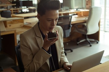 Executive using laptop while talking on mobile phone