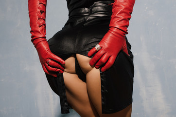 Sexy woman in a dress with a cut back stand in red gloves holding herself in the ass