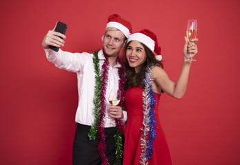 Portrait young couple taking a selfie smiling while celebrating christmas and happy new year on red background.