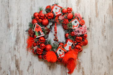 Christmas Wreath decorated with red balls, bows, roses and toy houses