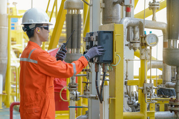 Production operator operating centrifugal oil pump by using local mode to start and another hand using walkie talkie to talk with central control room, offshore oil and gas industry business.