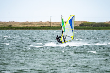 Man windsurfing close to the town of Caernarfon in Wales - United Kingdom