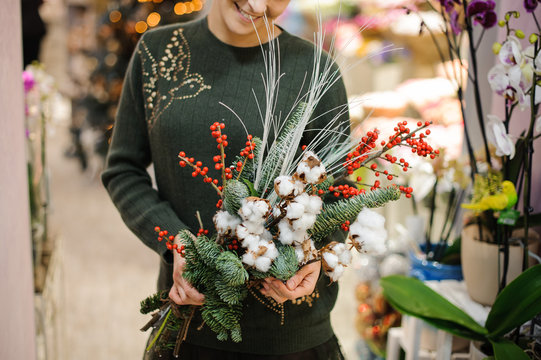 Woman holding a winter Christmas bouquet made of fir tree, cotton and berries