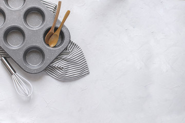 Kitchen utensils for baking - Cupcake metal mold, Whisk, wooden spoons on Crumpled Striped Napkin.