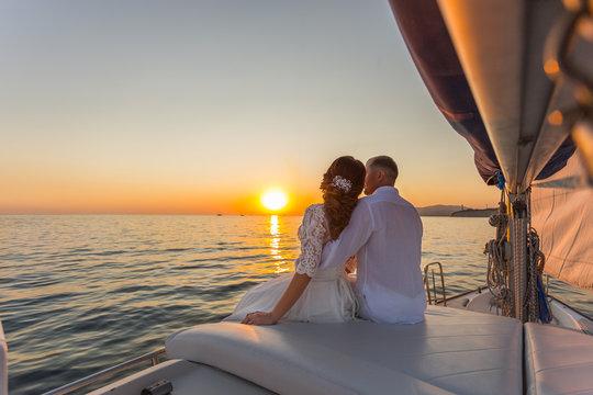 wedding couple travel on yacht at sunset