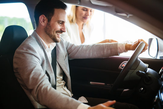 Portrait of handsome young man taking luxury car for test drive, sitting inside and smiling