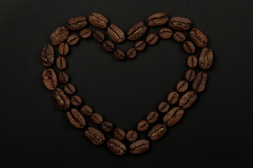 Roasted coffee beans placed in a shape of heart on black background