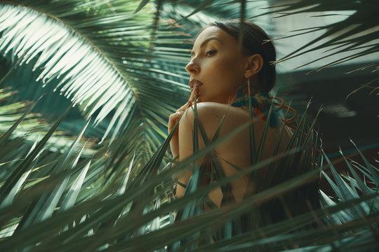 Portrait exotic woman among tropical plants, fashion, beauty, co