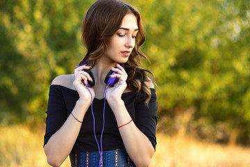 portrait of a beautiful girl witn headphones on her neck, young woman listening to music on nature