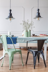 Black and green chair at table in modern dining room interior with lamps and flowers. Real photo