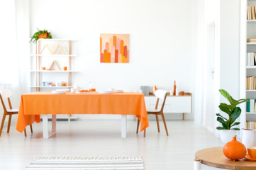 Real photo of dining room in vivid color. Orange tablecloth on long table with white chairs