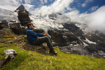 Resting tourist with a mountain landscape on bacground nearby resort of Kandersteg, Switzerland