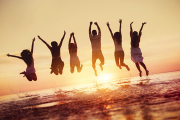 Group of happy friends jumps in sunset water