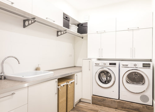 Laundry room with washing machine in modern house