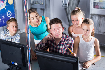Parents with their children are using PC in time having fun together