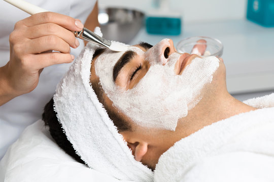 Good looking man receiving facial mask with rejuvenating effects in spa beauty salon.