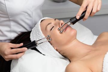 Beautiful woman receiving facial microcurrent treatment at spa salon. Beautician using electrical...
