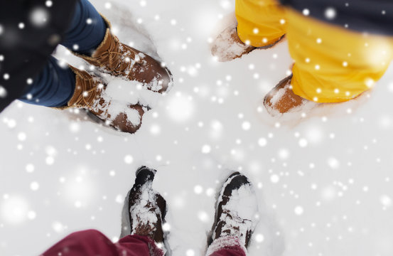season, friendship and people concept - feet on snow