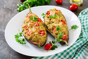 Minced meat chicken and vegetables stuffed eggplants on a grey background. Dinner food.
