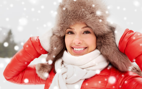 people, season and leisure concept - happy woman in winter fur hat outdoors