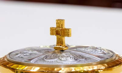 Gold cross on silver container White background,The sign of faith in God.