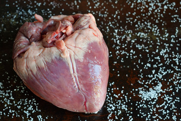 Heart before cooking on black background. Raw meat. Offal