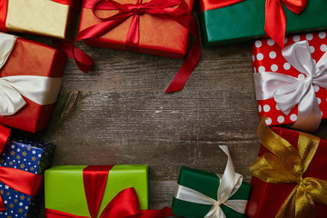 flat lay with presents wrapped in different wrapping papers with ribbons on wooden surface, christmas background
