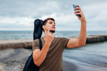 Young man carrying acoustic guitar and taking selfie using phone on cloudy beach. Guy shows rockstar symbol