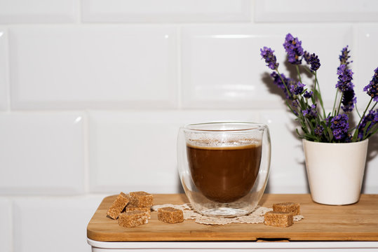 A cup of coffee, lumps of sugar and a vase with aromatic lavender