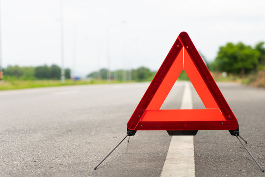 breakdown triangle symbol stands near broken car alongside the road. Car broke down on the road. Broken car accident sign on a road concept.