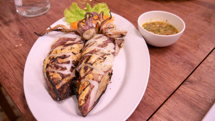 Grilled squid on dish with sauce.