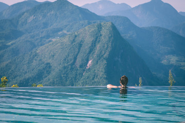 Vacations of Woman relax in tropical infinity pool above the Mountain peak in the morning in front of beautiful nature views in SAPA vietnam,Feel so Happiness and comfortable in holidays