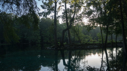 Reflection of the cypress forest in turquoise crystal clear waters of the lagoon of Ginnie Springs, Florida. USA