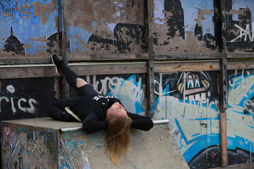 A girl in dark clothes dances 'Vogue' dance on a sports ground for skateboarders with painted graffiti walls