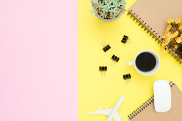 Flat lay design of travel summer concept - Top view of notebook, airplane, tree, flower, coffee, clip and wireless mouse on pink and yellow pastel color copy space. travel on pastel color background.